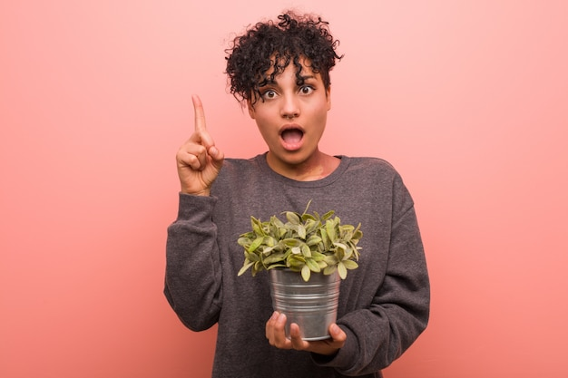 Jeune femme afro-américaine tenant une plante détendue pensant à quelque chose à un.