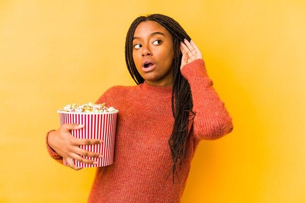 Jeune femme afro-américaine tenant un pop-corn isolé essayant d'écouter un commérage.