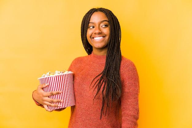 Jeune femme afro-américaine tenant un pop-corn isolé regarde de côté souriant, gai et agréable.