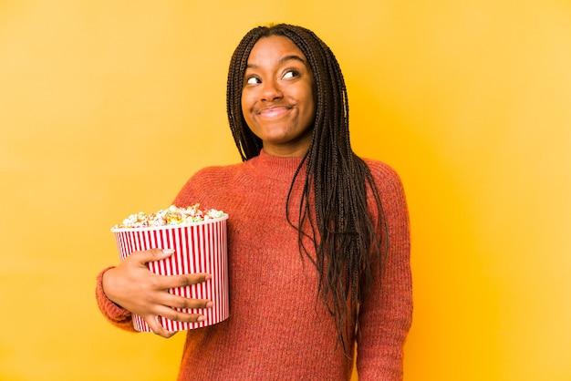 Jeune femme afro-américaine tenant un pop-corn isolé rêvant d'atteindre les objectifs et les buts