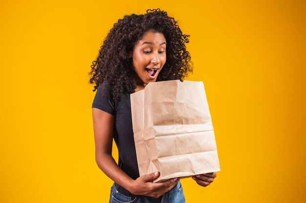 Jeune femme afro-américaine tenant un sac en papier à emporter souriant heureux sur fond jaune