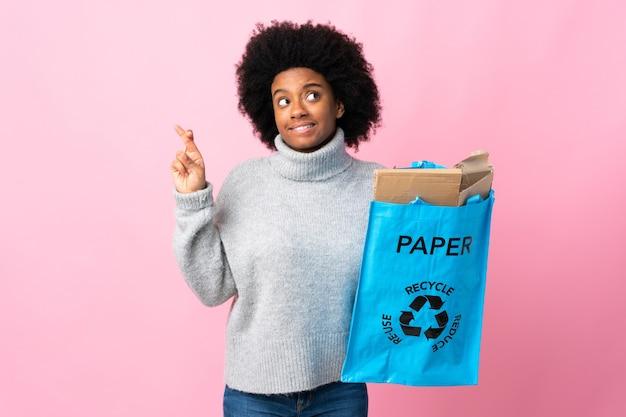 Jeune femme afro-américaine tenant un sac de recyclage avec les doigts croisés et souhaitant le meilleur