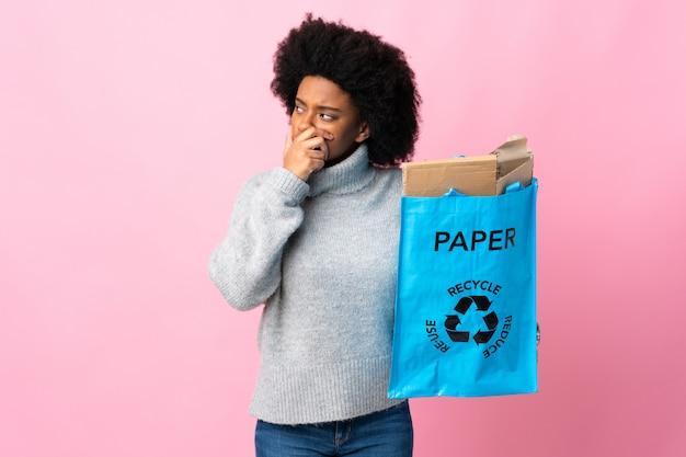 Jeune femme afro-américaine tenant un sac de recyclage isolé sur coloré ayant des doutes et avec l'expression du visage confus