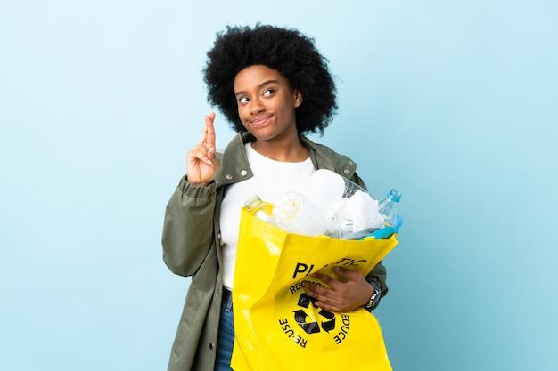 Jeune femme afro-américaine tenant un sac de recyclage isolé sur fond coloré avec les doigts qui se croisent et souhaitant le meilleur