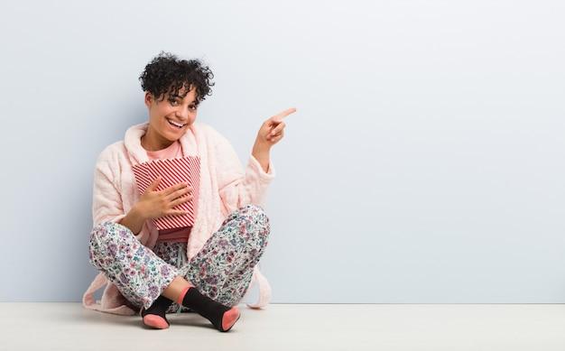 Jeune femme afro-américaine tenant un seau de maïs soufflé souriant joyeusement pointant avec l'index loin.