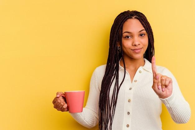 Jeune femme afro-américaine tenant une tasse isolée montrant le numéro un avec le doigt.