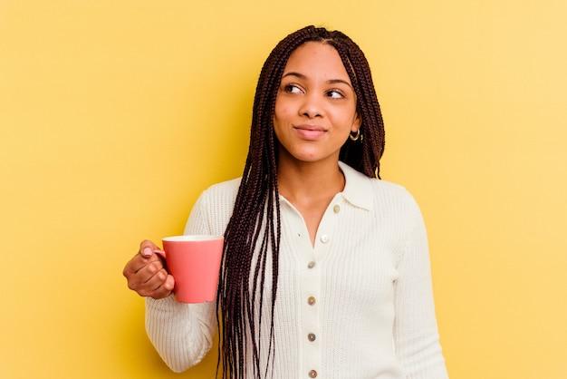 Jeune femme afro-américaine tenant une tasse isolée rêvant d'atteindre les objectifs et les buts