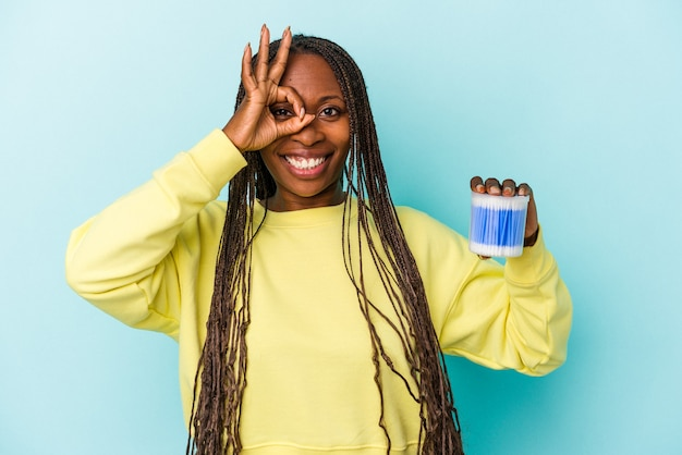 Jeune femme afro-américaine tenant des taureaux de coton isolés sur fond de bourgeons excités en gardant un geste ok sur les yeux.
