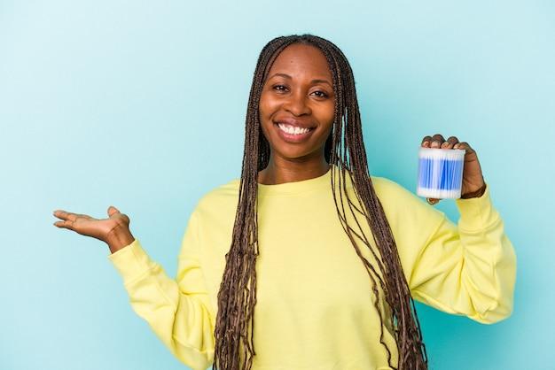 Jeune femme afro-américaine tenant des taureaux de coton isolés sur fond de bourgeons montrant un espace de copie sur une paume et tenant une autre main sur la taille.