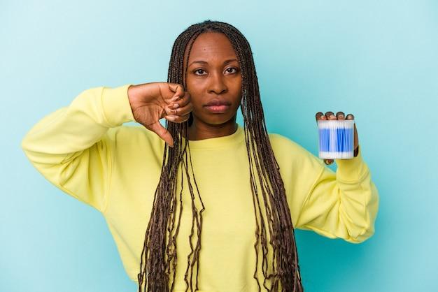 Jeune femme afro-américaine tenant des taureaux de coton isolés sur fond de bourgeons montrant un geste d'aversion, les pouces vers le bas. notion de désaccord.