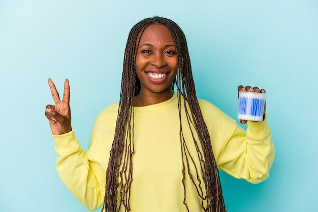 Jeune femme afro-américaine tenant des taureaux de coton isolés sur fond de bourgeons montrant le numéro deux avec les doigts.