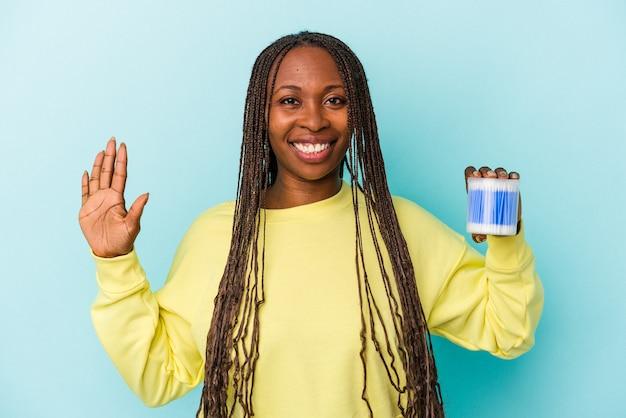 Jeune femme afro-américaine tenant des taureaux de coton isolés sur fond de bourgeons souriant joyeux montrant le numéro cinq avec les doigts.