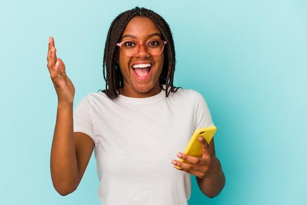 Jeune femme afro-américaine tenant un téléphone portable isolé sur fond bleu recevant une agréable surprise, excitée et levant les mains.
