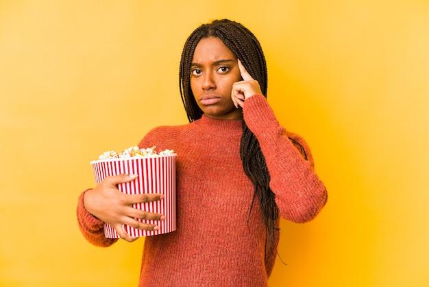 Jeune femme afro-américaine tenant un temple de pointage isolé pop-corn avec le doigt, pensant, concentré sur une tâche.