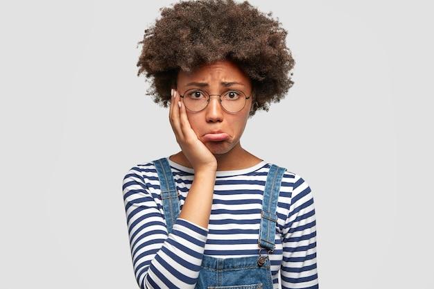 Une jeune femme afro-américaine terne et terne a une expression triste