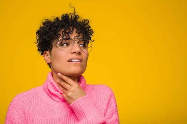 Une jeune femme afro-américaine vêtue d'un pull rose a mal à la gorge à cause d'un virus ou d'une infection.