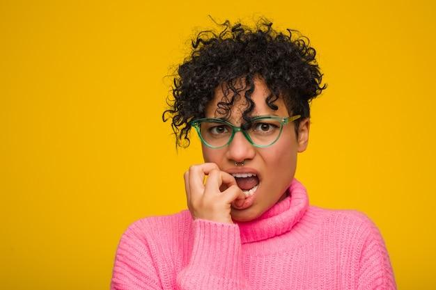 Jeune femme afro-américaine vêtue d'un pull rose se ronger les ongles, nerveuse et très inquiète.