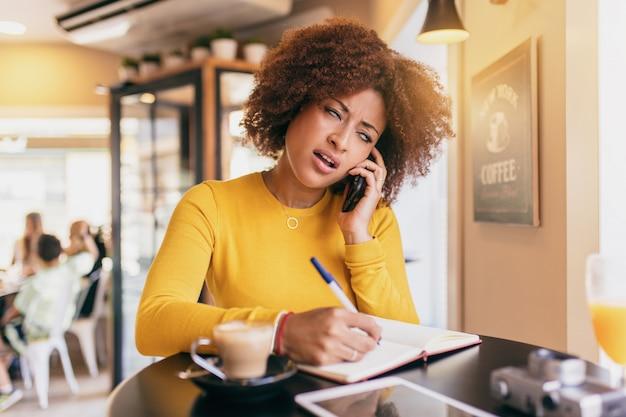 Jeune femme afro au café, parlant au téléphone mobile, très décontenancée et dépassée, écrivant