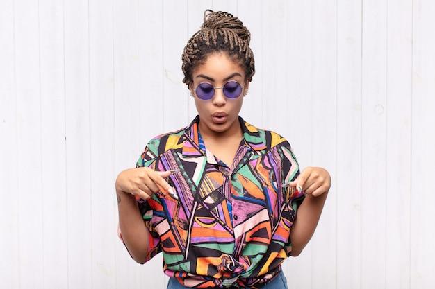 Jeune femme afro avec la bouche ouverte pointant vers le bas avec les deux mains, l'air choqué, étonné et surpris