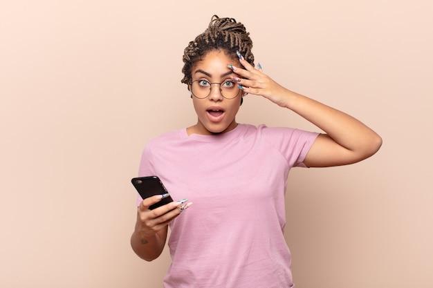 Jeune femme afro à la choqué, effrayé ou terrifié, couvrant le visage avec la main et furtivement entre les doigts