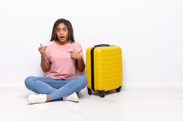 Jeune femme afro à la choqué et surpris avec la bouche grande ouverte, pointant vers soi. concept de vacances