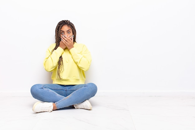 Jeune femme afro couvrant la bouche avec les mains avec une expression choquée et surprise isolée