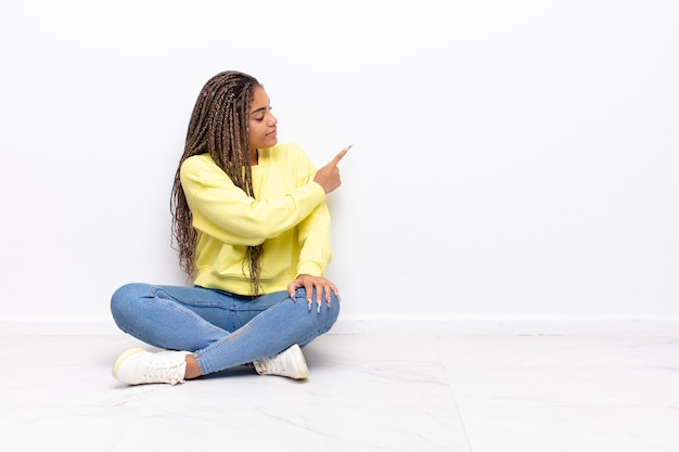 Jeune femme afro debout et pointant vers l'objet sur l'espace de copie, vue arrière