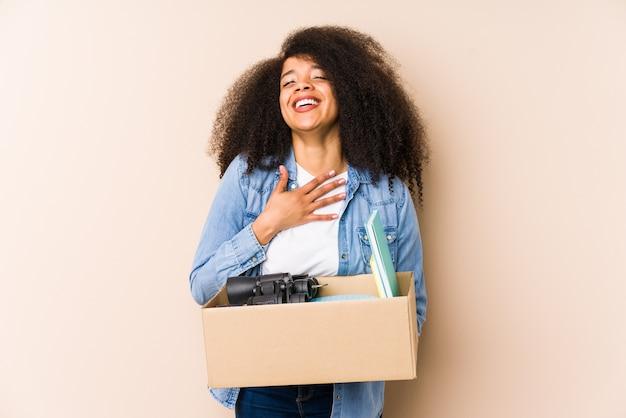 Jeune femme afro déménageant à la maison isolée jeune femme afro éclate de rire en gardant la main sur la poitrine.