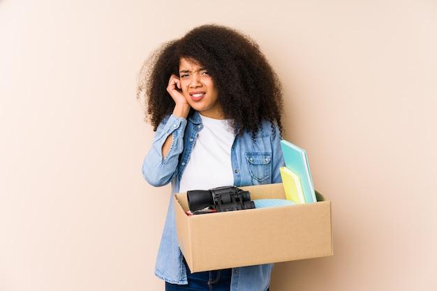 Jeune femme afro déménager isolé. jeune femme afro couvrant les oreilles avec les mains.