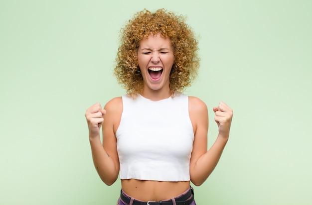 Jeune femme afro à extrêmement heureux et surpris, célébrant le succès, criant et sautant contre le mur vert