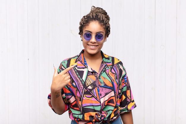 Jeune femme afro à la fierté, confiante et heureuse, souriante et pointant vers soi ou faisant signe numéro un