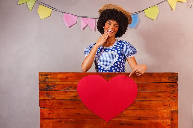 Jeune femme afro habillée pour la fête junina derrière une planche de bois avec un coeur