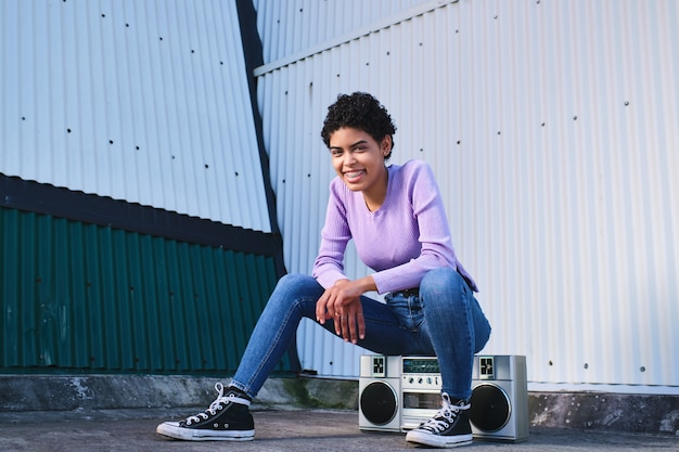 Jeune femme afro latina assise sur un boom box avec une attitude heureuse et insouciante