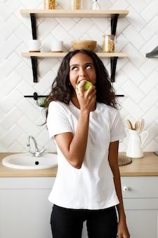 Jeune femme afro mange une pomme et lève les yeux