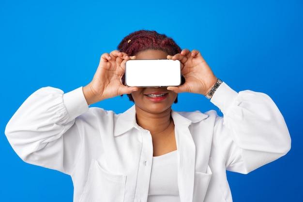 Jeune femme afro montrant un écran de smartphone vierge sur fond bleu