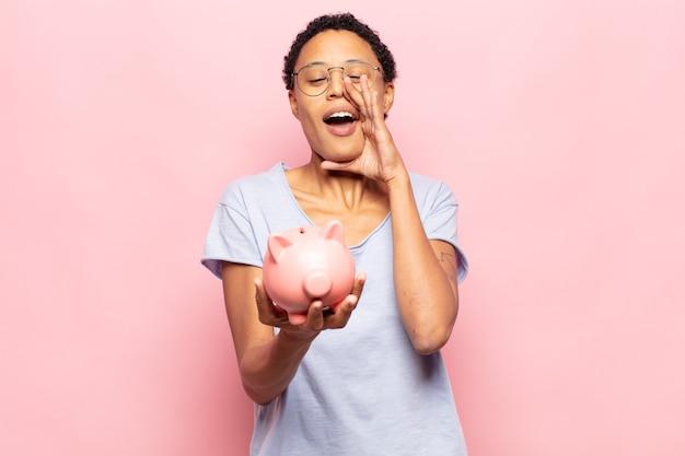 Jeune femme afro noire se sentant heureuse, excitée et positive, donnant un grand cri avec les mains à côté de la bouche, appelant