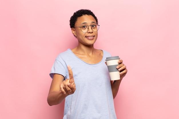 Jeune femme afro noire souriant fièrement et en toute confiance faisant le numéro un pose triomphalement, se sentant comme un leader