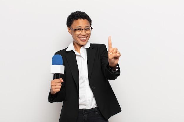 Jeune femme afro noire souriante et à la sympathique, montrant le numéro un ou d'abord avec la main vers l'avant, compte à rebours
