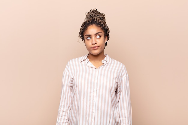 Jeune femme afro à la perplexité et à la confusion, se demandant ou essayant de résoudre un problème ou une réflexion