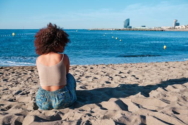 Jeune femme afro à la plage de barcelone tôt le matin