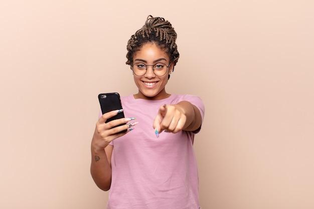 Jeune femme afro pointant la caméra avec un sourire satisfait, confiant et amical, vous choisissant
