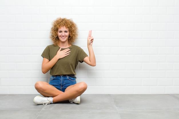 Jeune femme afro à la recherche de bonheur, confiant et digne de confiance, souriant et montrant le signe de la victoire, avec une attitude positive assis sur un sol