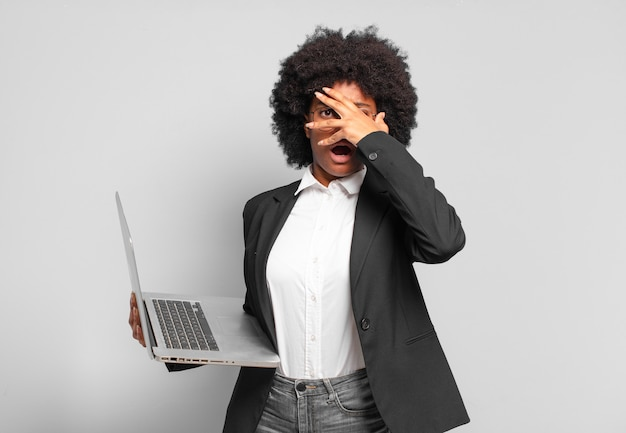 Jeune femme afro à la recherche de choc, effrayé ou terrifié, couvrant le visage avec la main et jetant un œil entre les doigts concept d'entreprise