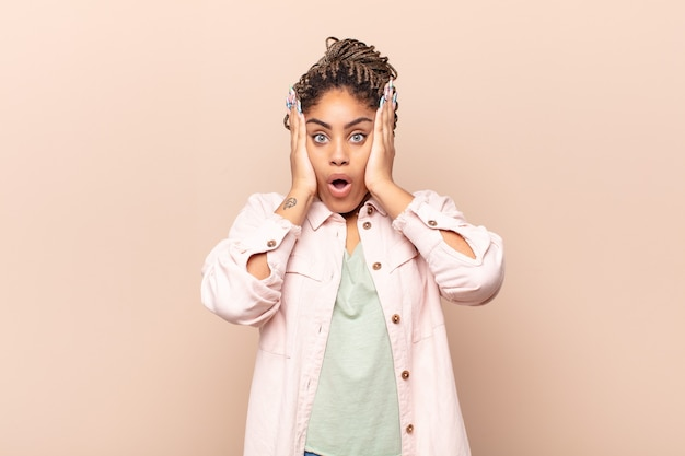 Jeune femme afro à la recherche désagréablement choquée, effrayée ou inquiète