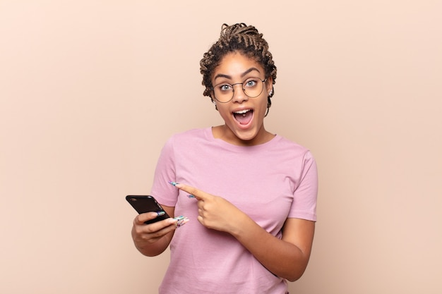 Jeune femme afro à la recherche excitée et surprise en pointant vers le côté et vers le haut pour copier l'espace. concept de téléphone intelligent