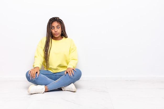 Jeune femme afro à la recherche de goofy et drôle avec une expression idiote aux yeux croisés, plaisantant et s'amusant