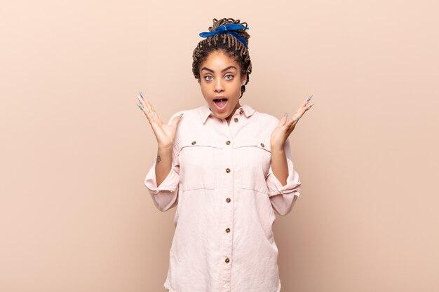 Jeune femme afro à la recherche heureuse et excitée, choquée par une surprise inattendue avec les deux mains ouvertes à côté du visage