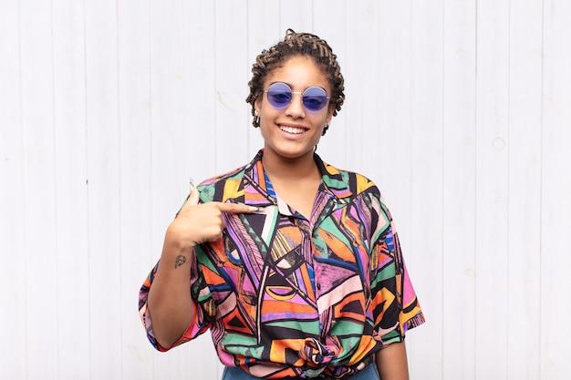 Jeune femme afro à la recherche de plaisir, fier et surpris, pointant joyeusement vers soi, se sentant confiant et élevé