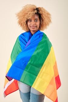 Jeune femme afro regardant dans la caméra tout en couvrant d'un drapeau de la fierté gaie sur un fond isolé. concept de communauté lgbtq.