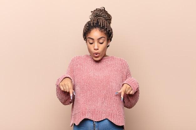 Jeune femme afro se sentant choquée et surprise, souriante, prenant la main à cœur, heureuse d'être celle ou montrant sa gratitude